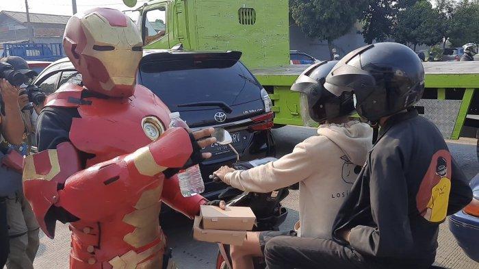 Polisi libatkan maskot Ironman dan pahlawan super di kegiatan bagi-bagi makanan di pos penyekatan Sasak Jarang Bekasi, Jumat (16/7/2021).