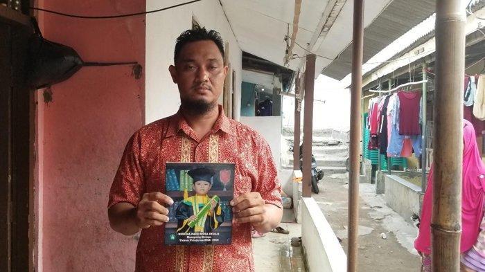 Supriyadi yang menunjukan foto almarhum Husein (8) keponakannya yang meninggal setelah hanyut di Sungai Cisadane, Senin (26/8/2019)