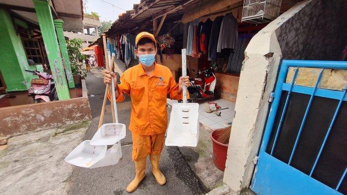 Syaiful Effendi sedang menyapu jalan menggunakan pengki buatannya dari jeriken bekas pada Kamis (10/6/2021).