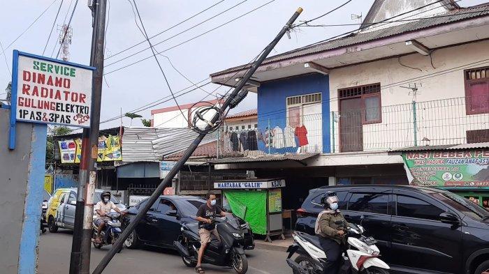 Tiang kabel utilitas interter miring nyaring menutup Jalan Raya Mustikasari, Kecamatan Mustikajaya, Kota Bekasi, Selasa (31/3/2021)