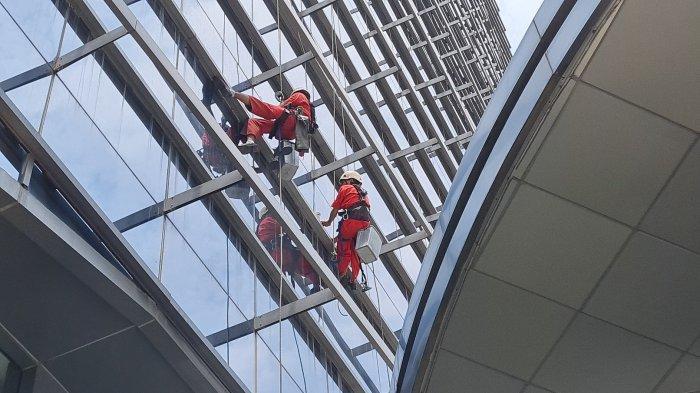 Vian dan Irfan sedang membersihkan kaca gedung L'Avenu di Pancoran, Jakarta Selatan pada Jumat (24/9/2021).