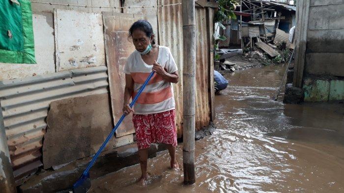 Warga Kampung Arus, Kelurahan Cawang saat membersihkan timbunan lumpur bercampur sampah sisa banjir di Kramat Jati, Jakarta Timur, Minggu (25/10/2020).