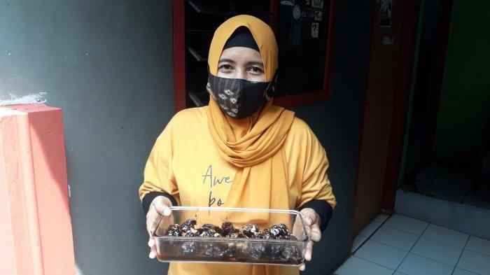 Warga Lenteng Agung RT 004 RW 008, Purwanti (40) memegang semur kerbau andil hasil buatannya kepada TribunJakarta.com pada Rabu (12/5/2021).