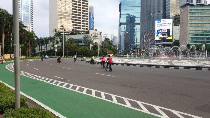 Sejumlah warga tampak asyik berolahraga di sekitar kawasan Sudirman-Thamrin, Jakarta Pusat saat PPKM Level 4, Minggu (8/8/2021).