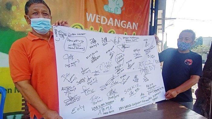 Warga setempat membentangkan kain putih berisi tanda tangan dukungan terhadap eks Lurah Gajahan Suparno yang dipecat Wali Kota Solo Gibran, Senin (3/5/2021).
