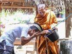 foto-seorang-biksu-yang-sedang-membantu-seorang-pria-berwudu.jpg
