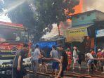 petugas-damkar-dibantu-warga-memadamkan-api-di-kios-yang-terbakar-di-jalan-minangkabau-barat.jpg