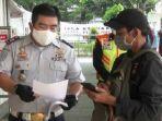 petugas-di-stasiun-depok-baru-mengecek-surat-tugas-yang-dibawa-pekerja.jpg