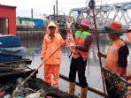 petugas-upk-badan-air-jakarta-barat-temukan-ikan-koi-saat-bersihkan-sampah-pascabanjir.jpg
