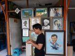 seorang-pedagang-atau-seniman-cecep-di-depan-kiosnya-di-sentra-lukisan.jpg