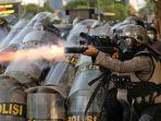 seorang-polisi-menembakkan-pelontar-gas-air-mata-saat-kericuhan-dalam-unjuk-rasa.jpg
