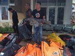 seorang-pria-mengangkat-jenazah-korban-gelombang-tsunami-anyer-yang-diduga-masih-balita.jpg