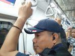 seorang-sekuriti-memakai-earphone-pada-kupingnya-di-dalam-kereta-mrt-jakarta-kamis-2832019.jpg
