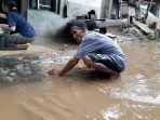 warga-kampung-arus-kelurahan-cawang-saat-membersihkan-timbunan-lumpur.jpg