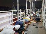 warga-pasar-gembrong-ramai-ramai-menjalankan-ibadah-salat-terawih-di-jembatan-penyeberang-orang_20180516_211527.jpg