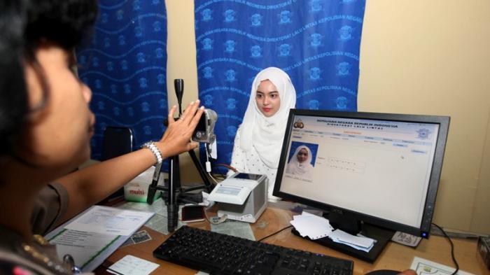 Seorang warga melakukan pemotretan untuk mengurus Surat Izin Mengemudi (SIM) di Mapolrestabes Makassar, Sulawesi Selatan.