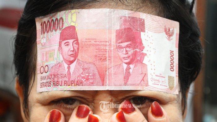 Seorang warga ibukota yang tidak mau disebutkan namanya memperlihatkan selembar uang palsu dengan nominal Seratus Ribu Rupiah, yang didapatnya dari customer, Rabu (11/6)