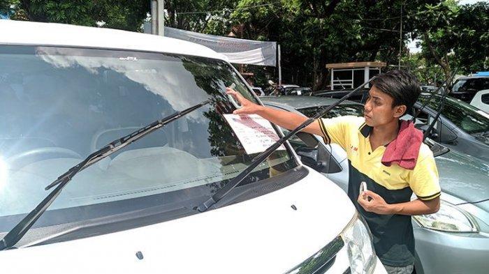 Seorang pedagang memasang kertas berisi spesifikasi mobil yang akan dijual di bursa mobil Sriwedari, Solo, Jawa Tengah