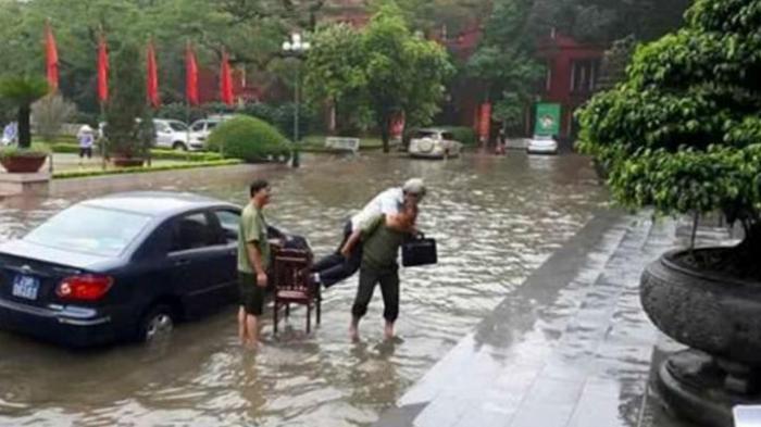 Foto yang menunjukkan adegan satpam menggendong pejabat di Ibu Kota Hanoi itu menyebar luas melalui jejaring internet