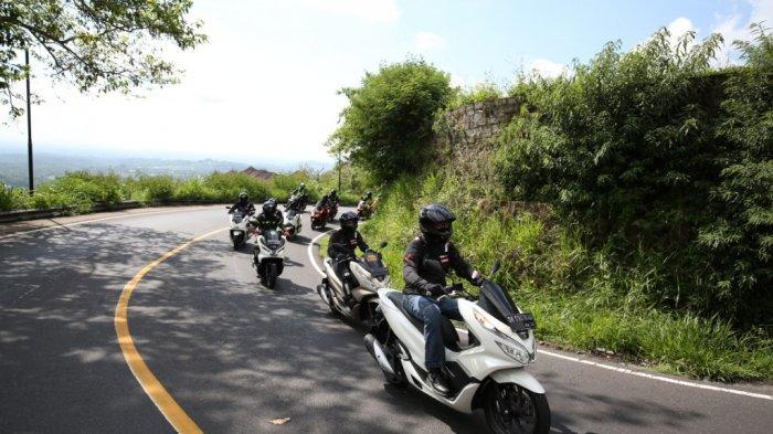 Berkendara menggunakan sepeda motor.