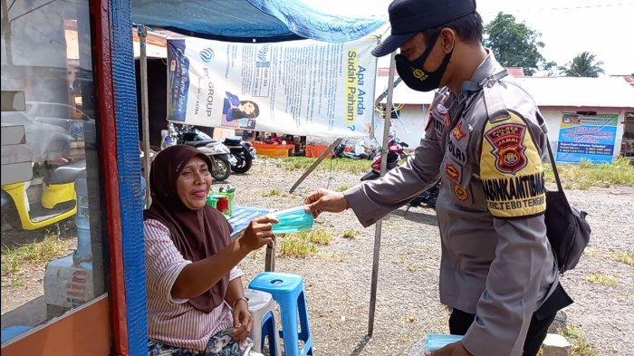 Bhabinkamtibmas Kelurahan Muara Tebo Bagikan Masker ke Pedagang Pasar