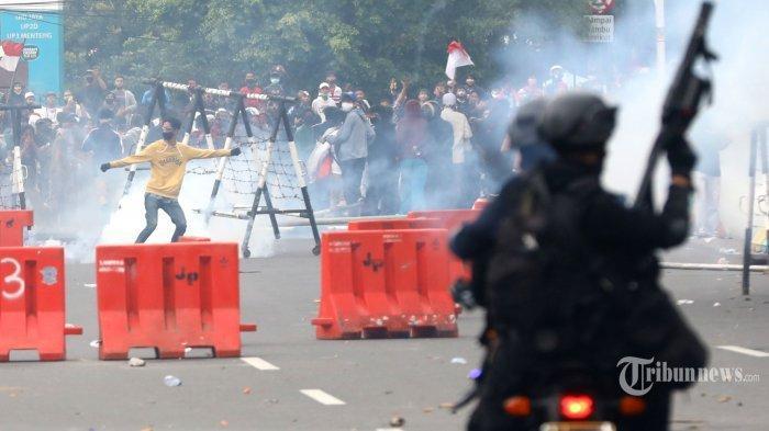 TRIBUNNEWS/IRWAN RISMAWAN Aparat kepolisian menembakkan gas air mata ke arah massa aksi saat demonstrasi di Gambir, Jakarta, Selasa (13/10/2020). Demonstrasi penolakan UU Cipta Kerja berakhir ricuh.