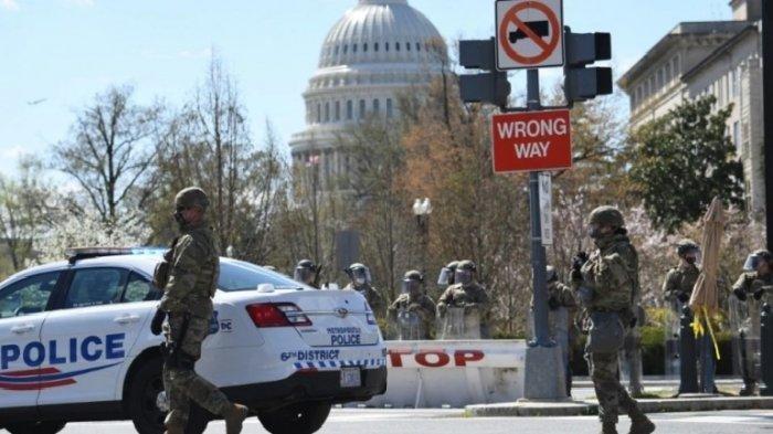 Pasukan garda nasional AS dan Polisi Gedung Capitol mengamankan komplek Gedung Kongres AS pasca serangan dengan menabrakkan kendaraan hari Jumat (2/4).