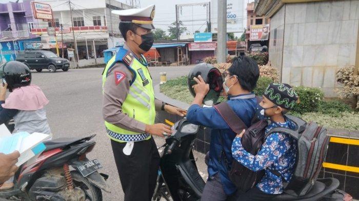 Perketat Penyebaran Covid-19, Personil Sat Lantas Polres Tebo Bagikan Masker ke Masyarakat