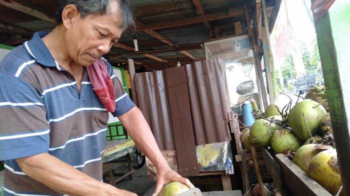 Samsul mengupas kelapa muda untuk pembelinya, Sabtu (05/09/2020).