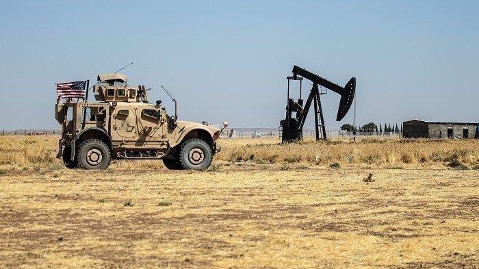 Kendaraan lapis baja militer AS berpatroli dekat ladang minyak Rumaylan di Provinsi Hasakeh yang dikuasai Kurdi Suriah pada 17 September 2020.