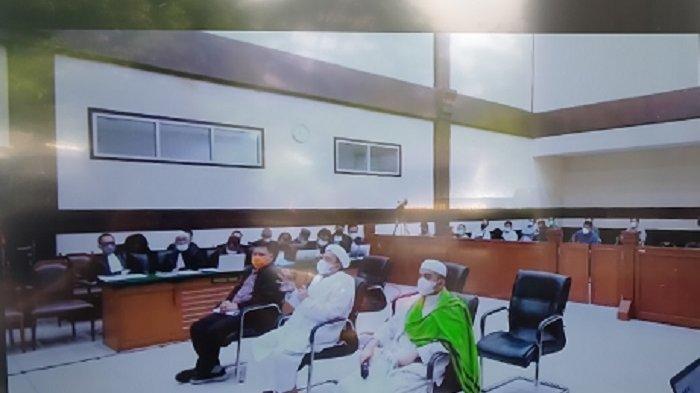 Terdakwa Muhammad Rizieq Shihab (Tengah), Hanif Alatas (Kanan dengan sorban hijau) dan Dirut RS UMMI Andi Tatat (Kiri) saat duduk sebagai terdakwa dalam sidang lanjutan hasil test swab palsu RS UMMI, di ruang sidang utama Pengadilan Negeri (PN) Jakarta Timur, Kamis (27/5/2021).