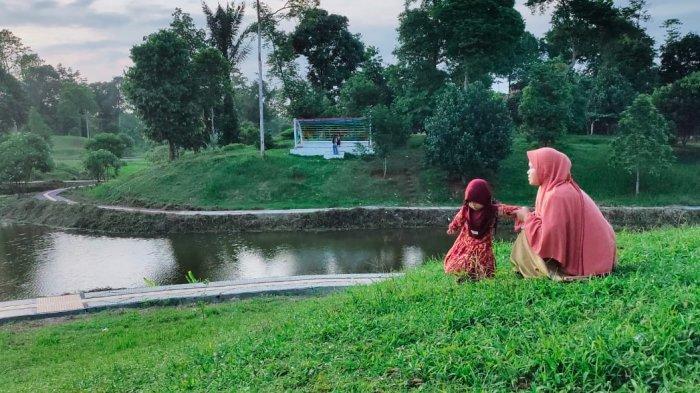 Pengunjung Taman Perkantoran Muara Sabak tengah menikmati suasana sekitar.