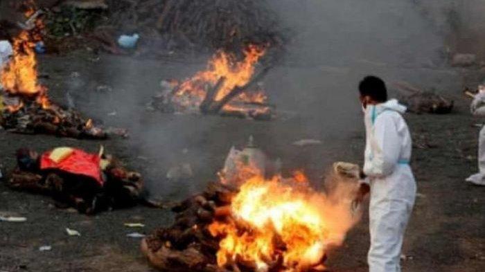 Petugas kesehatan di India melakukan kremasi pada jenazah.
