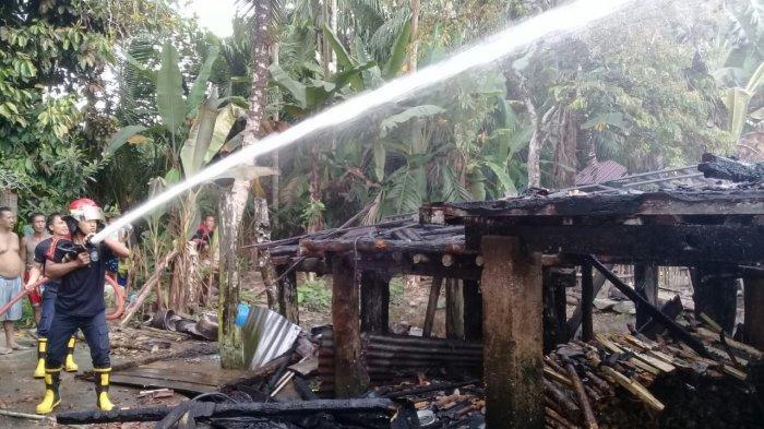 Petugas memadamkan api yang membakar rumah  panggung milik Ramzi