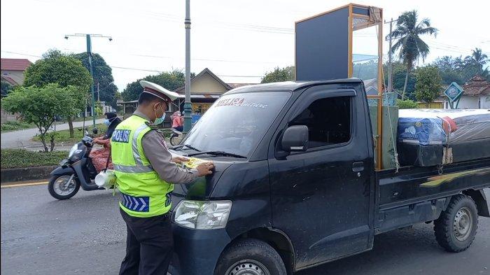 Personil Sat Lantas Polres Tebo bagikan masker dan tempelkan stiker ajakan pakai masker.