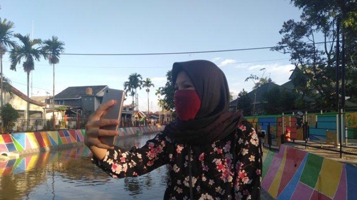 Halyzah Yani selfie sembari bersantai di tepian Taman Sungai Kota Baru, Selasa (6/10/2020).
