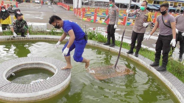 Sejumlah masyarakat dan polisi membersihkan Taman Air Mancur di Water Front City yang tak terurus.