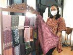 dhita-pemilik-galeri-rumah-batik-azmiah-memperlihatkan-hijab-motif-batik-yang-diproduksi.jpg