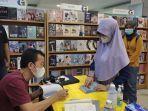 tere-liye-penulis-best-seller-sedang-menandatangani-buku.jpg
