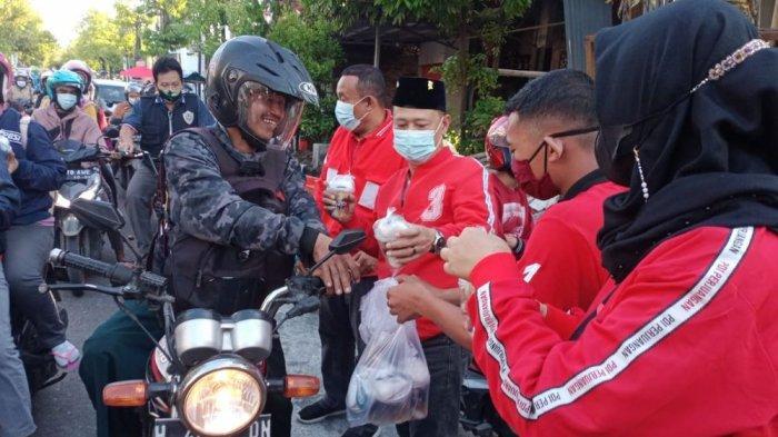 DPC PDIP Demak bagi-bagi takjik kepada sejumlah orang yang melintas di sepanjang Jalan Bhayangkara, Minggu (9/5/2021) sore.