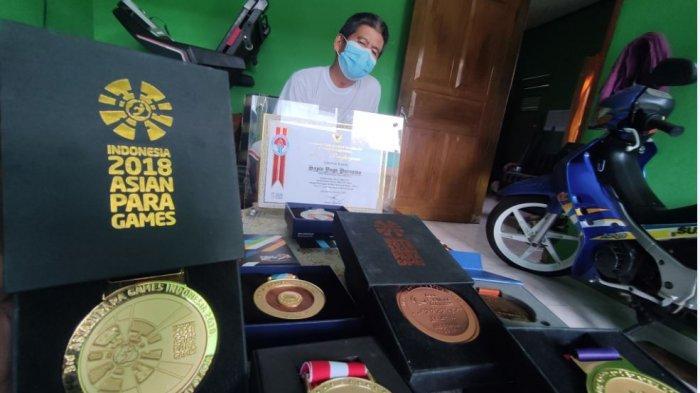 Tulus (55), ayah dari Sapto Yogo Purnomo atlet lari difable andalan Indonesia saat menunjukan berbagai medali dan penghargaan yang diraih anaknya itu di rumahnya di Desa Ciberung, RT 1 RW 3, Kecamatan Ajibarang, Kabupaten Banyumas, Rabu (1/9/2021).