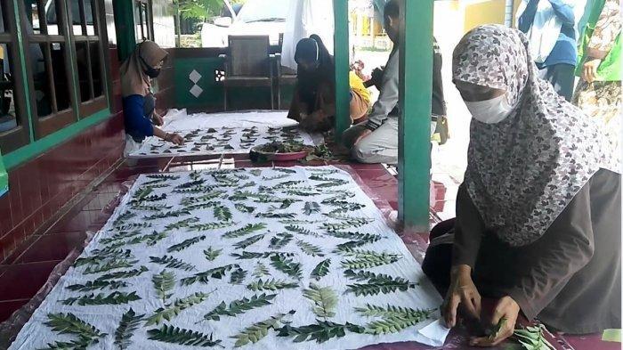 Perajin batik asal Desa Purworejo Kecamatan Ringinarum Kabupaten Kendal sedang membatik cap dengan dedaunan, Minggu (28/3/2021).