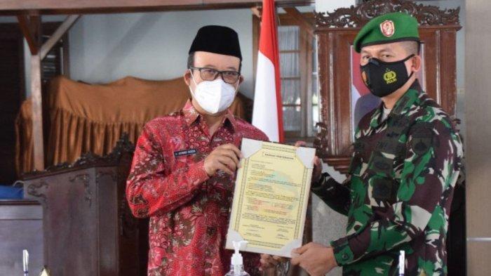 Bupati Banyumas, Achmad Husein bersama Dandim 0701 Banyumas, Letkol Inf Chandra saat menandatangani secara resmi Program TMMD Sengkuyung Tahap II yang dilaksanakan di Desa Gunung Wetan, Kecamatan Jatilawang Kabupaten Banyumas, Selasa (15/6/2021).