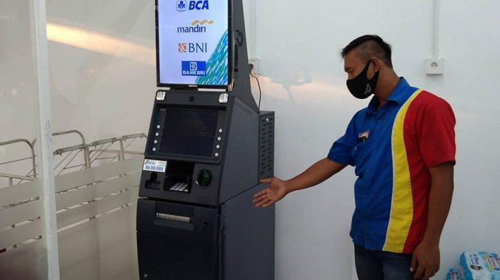 Karyawan Indomaret tunjukan mesin ATM bersama yang rusak di jalan Syuhada Raya, Tlogosar, Kota Semarang.