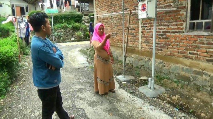 Uminingsih, Ketua RT 07, RW 04, Desa Majakerta, Kecamatan Watukumpul, Pemalang, berdiri di sebelah satu dari dua EWS, yang dipasang di desa, Selasa (6/4/2021).