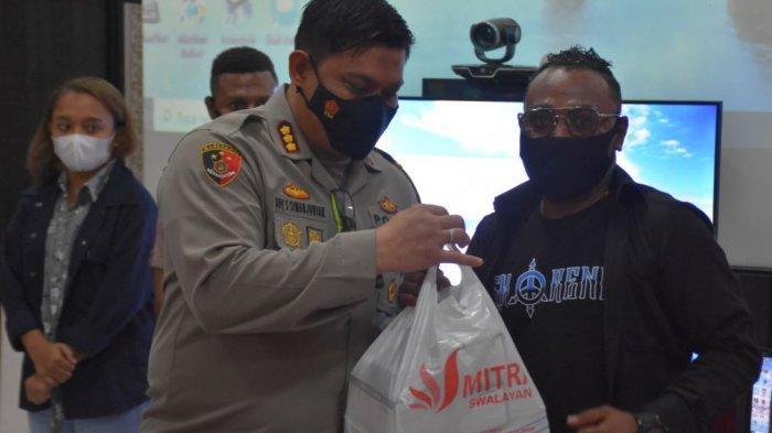 Kapolresta Solo Kombes Pol Ade Safri Simanjuntak ketika membagikan bingkisan kepada mahasiswa Papua dalam launching program Orang Tua Asuh bagi Putera Daerah Asli Papua di Aula Mapolresta Solo, Rabu (8/4/2021).