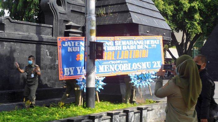 Petugas Satuan Polisi Pamong Praja Provinsi Jawa Tengah, sedang membersihkan karangan bunga bertuliskan #2021BaliJatidiri yang dipasang oleh suporter fanatik PSIS Semarang di pagar kantor Pemerintah Provinsi Jawa Tengah, Senin (21/12/20).