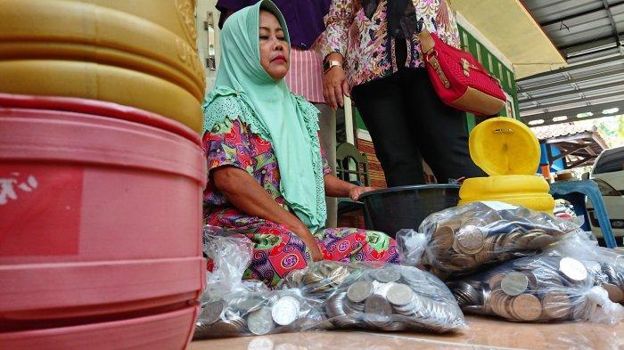 Karmi sedang menghitung uang koin di halaman rumahnya, yang terletak di Desa Kendaldoyong, Kecamatan Petarukan, Pemalang. Uang koin yang ia tabung di celengan plastik selama lima tahun, Rabu (3/3/2021).