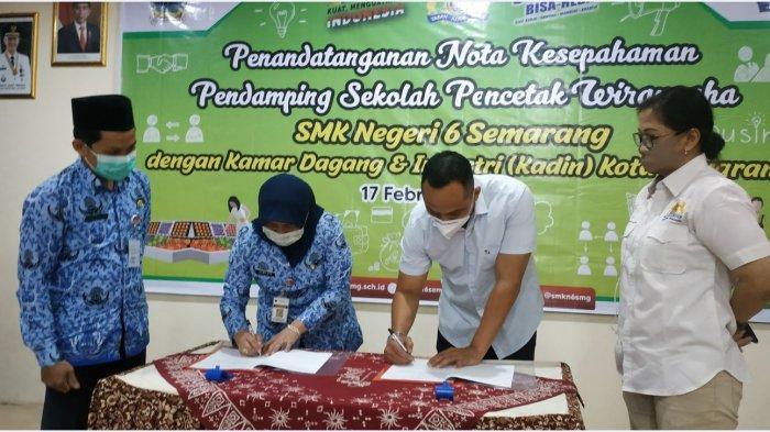 Kepala SMKN 6 Semarang, Almiati (kiri), dan Ketua Kadin Kota Semarang, Arnaz Agung Andrarasmara (kanan), menandatangani nota kesepahaman di Aula SMKN 6 Semarang, Rabu (17/2/2021). Kerja sama tersebut sebagai bentuk link dan match antara sekolah vokasi dengan industri dan dunia kerja (Iduka).