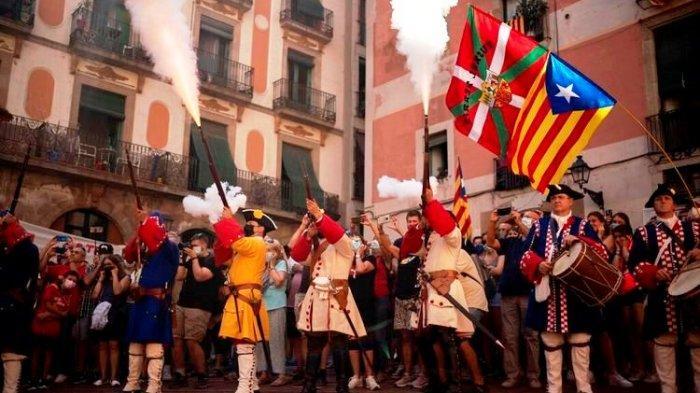 Pria berpakaian kostum menembakkan senapan mereka selama pertunjukan untuk merayakan Hari Nasional Catalonia di Barcelona, Spanyol, Sabtu, 11 September 2021.